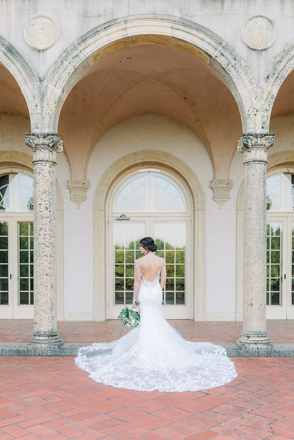 Bride in long wedding gown holding bouquet at Tulsa Philbrook bridal session
