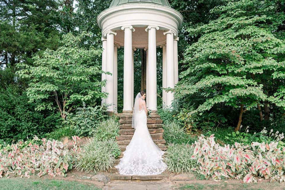 Bride on steps of gazebo with wedding train flowing down at Tulsa Philbrook bridal session