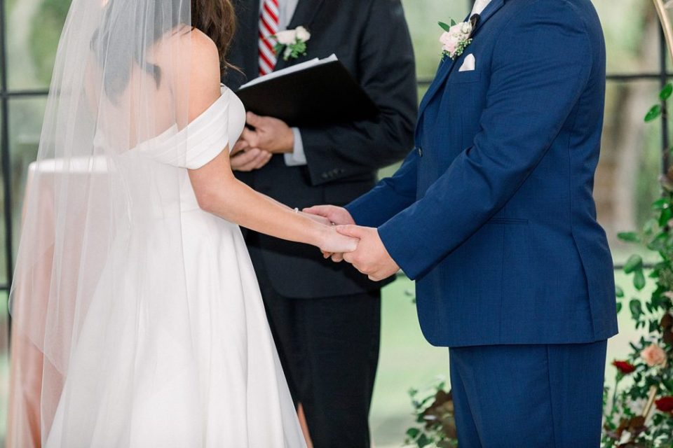 bride and groom holding hands at alter