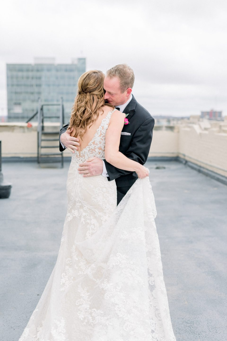 Groom and bride embracing on rooftop of Tulsa Club Hotel