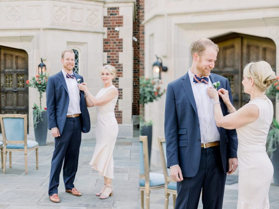 Mother of groom pinning boutonniere to groom outside Harwelden Mansion