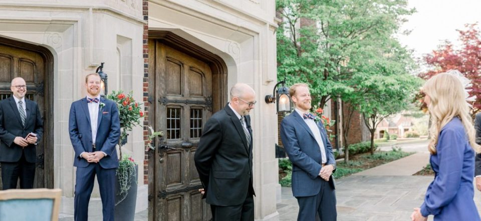 Groom grinning upon seeing bride at alter