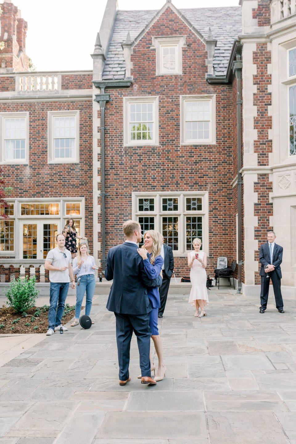 Bride and groom dancing in courtyard at Harwelden Mansion elopement