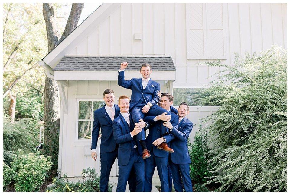 Groomsmen holding groom up in the air