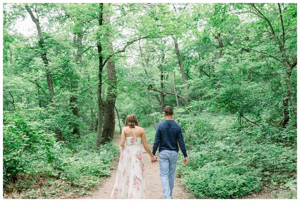 Couple walking through woods hand in hand