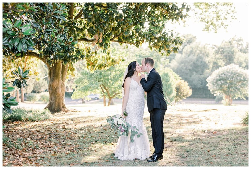 Bride and groom kiss under large tree