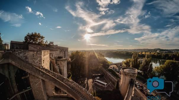 Bild aus Avignon mit viel Sonne und Wolken und den Mauern der Stadt