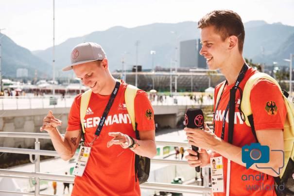 """Marcel und Nick stehen vor dem Paralympischen Spielstätten mit roten T-Shirts auf den """"Germany"""" steht."""
