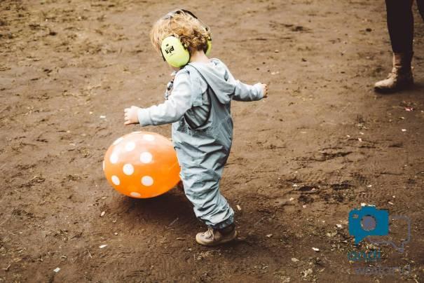 Ein Kleinkind mit Ohrschützern kickt einen Luftballon