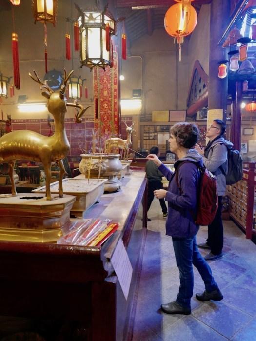 Amanda lighting incense at man mo temple