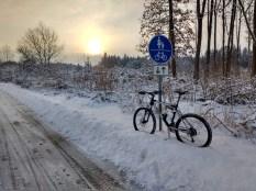Fahrrad an einen Schildpfosten gelehnt, die Sonne geht auf. Schnee überall