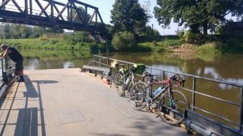 Zwei Fahrräder auf einer Flussfähre mit dem Fährmann im Hintergrund