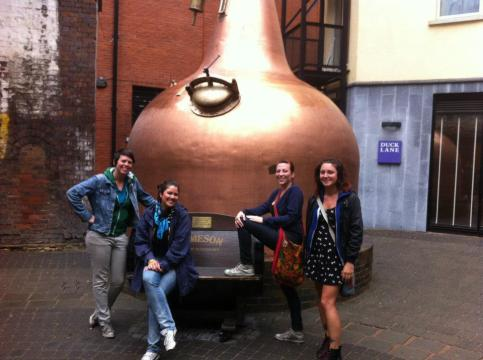In front of the distillery, posing like tourists next to a copper kettle.