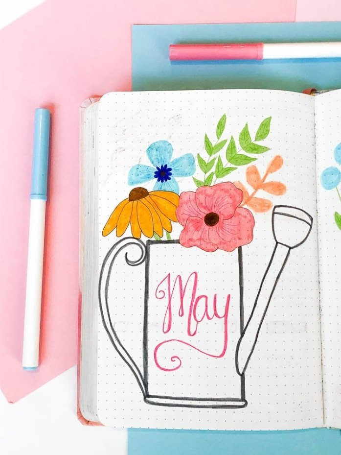 May bullet journal cover page with a watering can and wildflowers