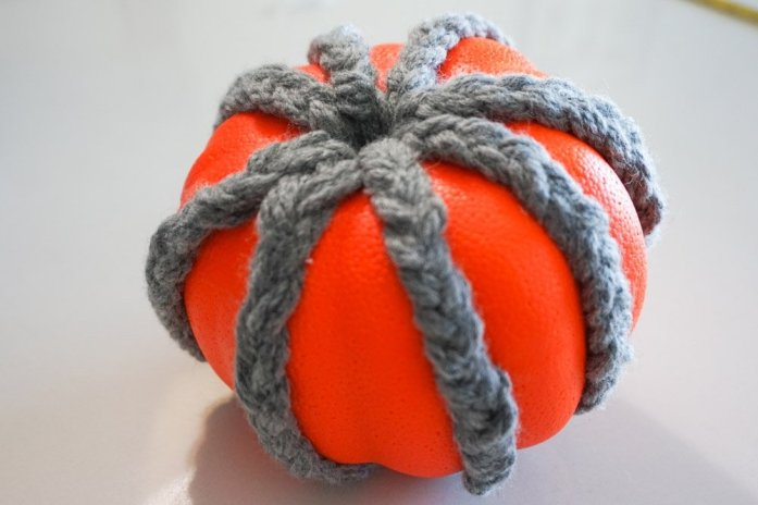 orange styrofoam pumpkin with grey braided yarn