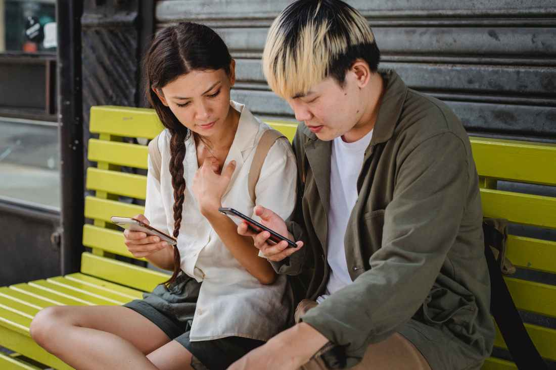 concentrated asian couple using smartphones on bench