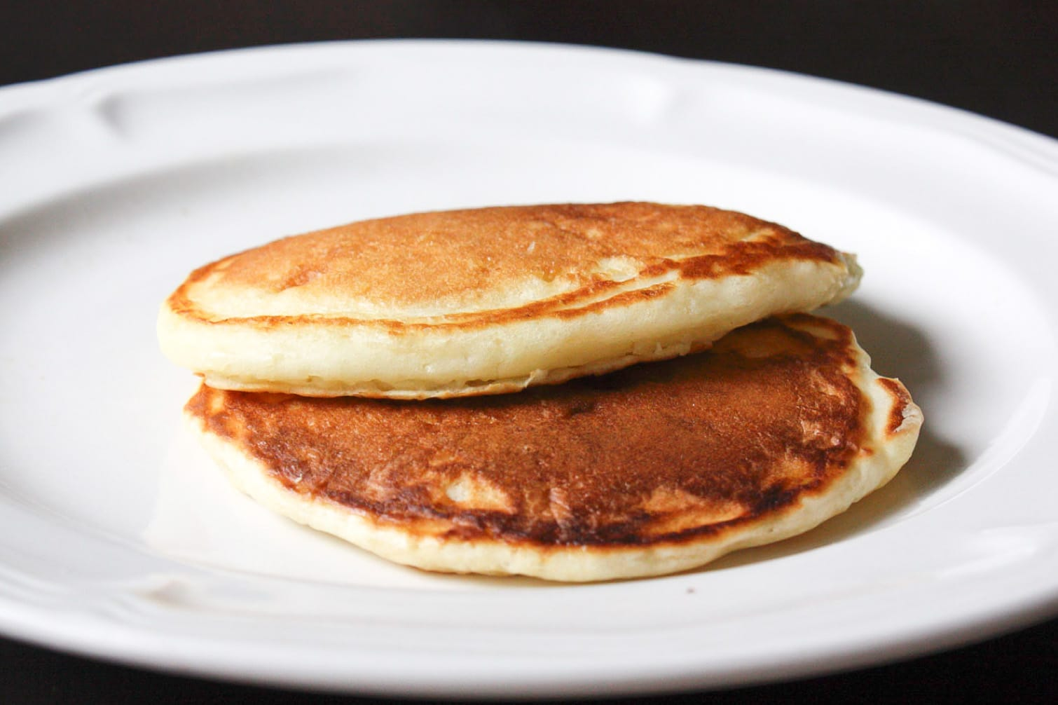 2 golden buttermilk pancakes stacked together on a white plate with a black background