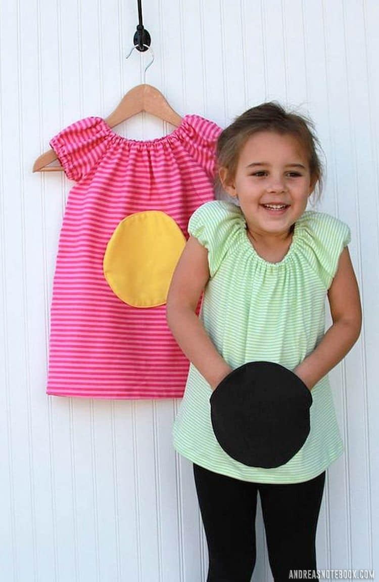 little girl with ponytail wearing green swing top with large round circle pocket. White wall behind with hanging pink dress and yellow circle pocket
