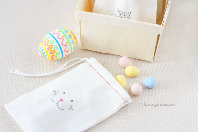 Draw a bunny face on a muslin bag with fabric pens