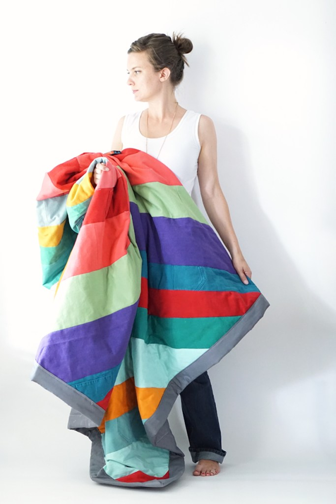 Gorgeous upcycled denim quilt with red, coral, sage green, purple and various colors of turquoise stripes. It is held by a woman in a white tank top and brown hair.