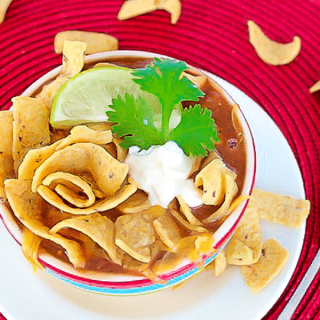 taco soup with fritos in a bowl on red placemat