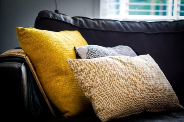 yellow and gray pillows of different sizes on sofa. Learn how to sew an envelope pillowcase so you can add more pillows to your sofa.