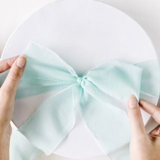 light blue bow tied on white round gift