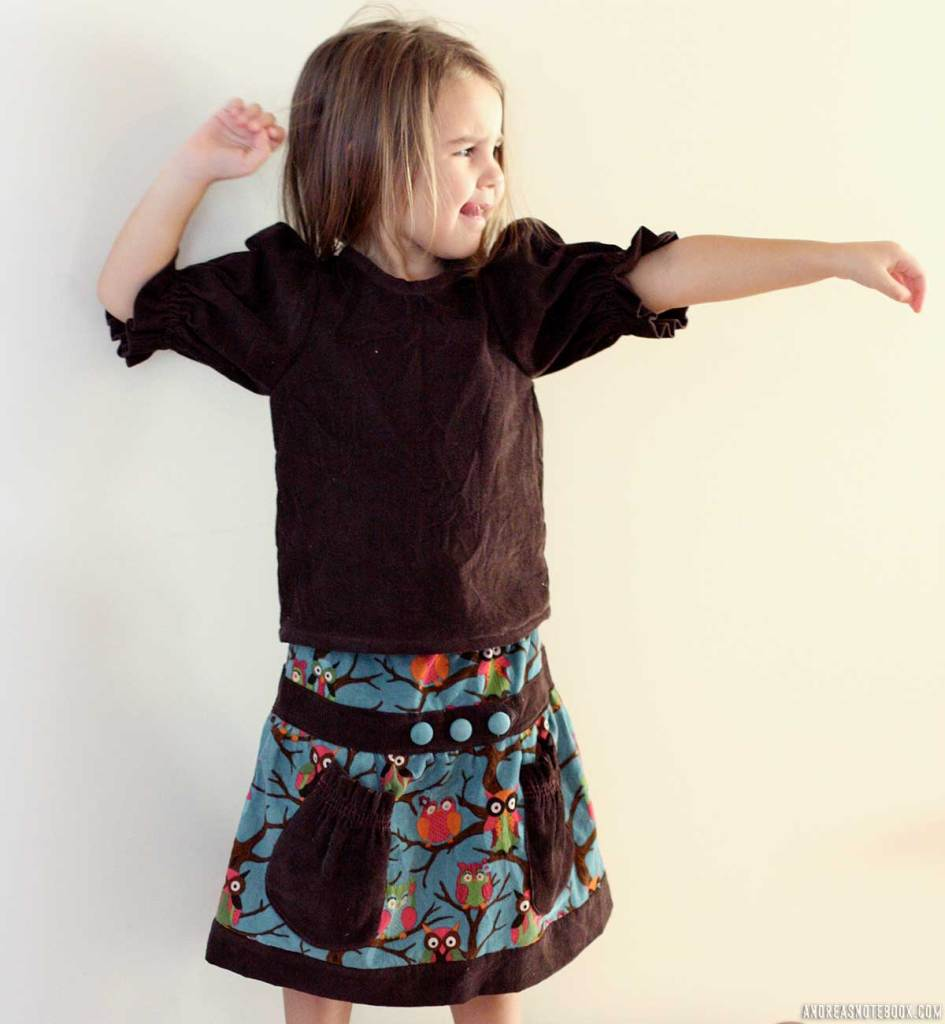 Cute little girl holds arms out while wearing a skirt with owls on it and a brown puffed sleeve shirt. Cute diy shirt.
