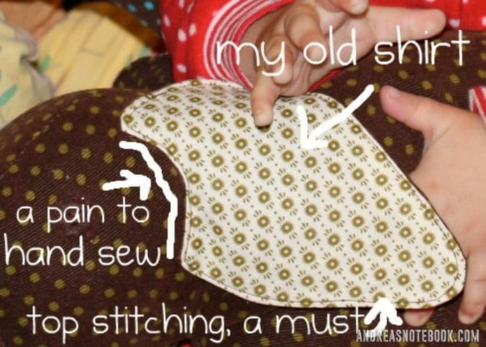 """close up of baby holding brown polkadot stuffed DIY elephant ears. Text points to elephant ear says """"my old shirt"""". Another arrow points to where the ear connects to the body says """"a pain to sew"""""""