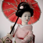 red-toned photo of a doll geisha