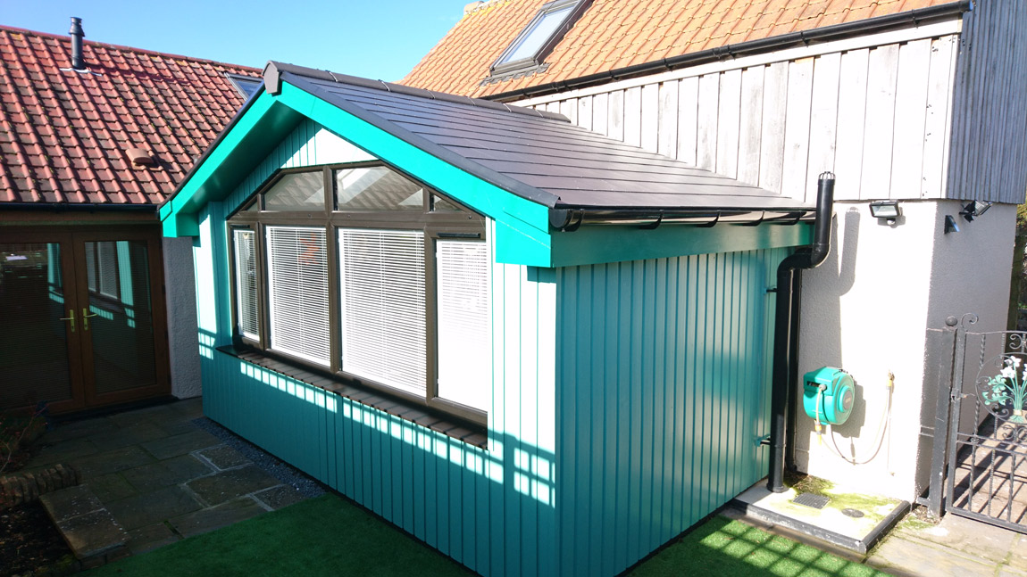 timber clad extension finished in green