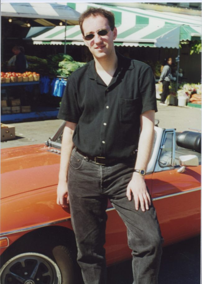 A younger version of me, posing in front of a car that isn't ours.