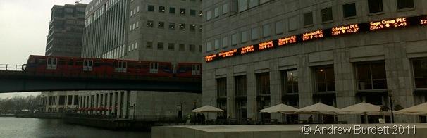 CANARY WHARF_The DLR runs through Canary Wharf. The orange text on the building's wall shows company stocks.