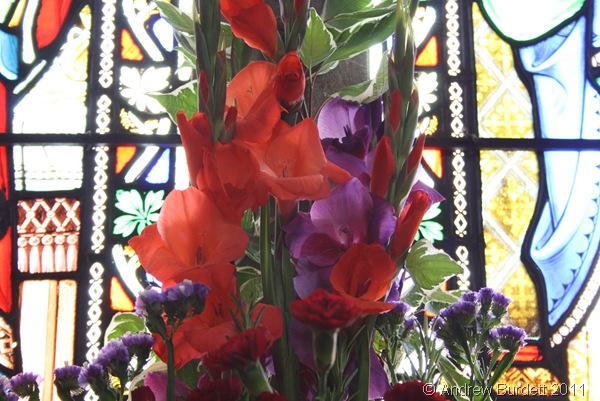 COLOUR COORDINATING_Flowers in front of a stained-glass window.