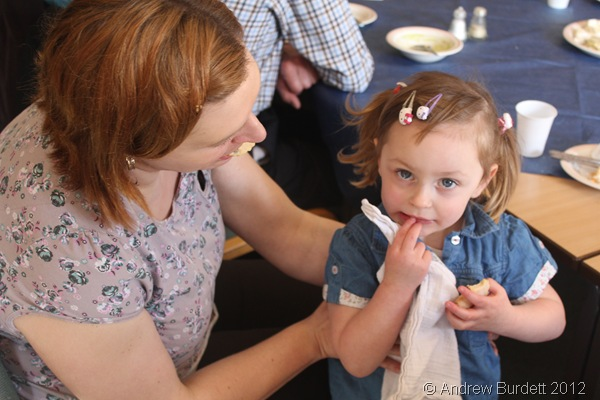 TWINKLE IN HER EYE: A girl enjoys a biscuit at the Lent Lunch this afternoon. (IMG_8615)