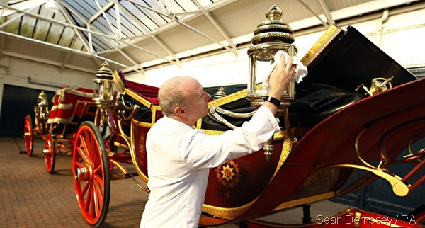 RIGHT ROYAL RUBDOWN: A man prepares the Royal Carriage ahead of Tuesday's procession. (_60557755_014881433-2)