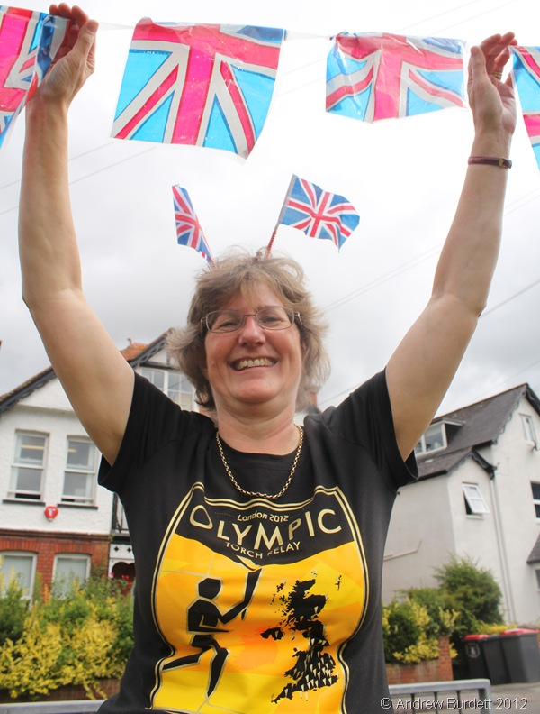 WAITING FOR THE TORCH: One of the ladies manning the drinks station along the route holds bunting ahead of the Torch passing. (IMG_8924_ARB)