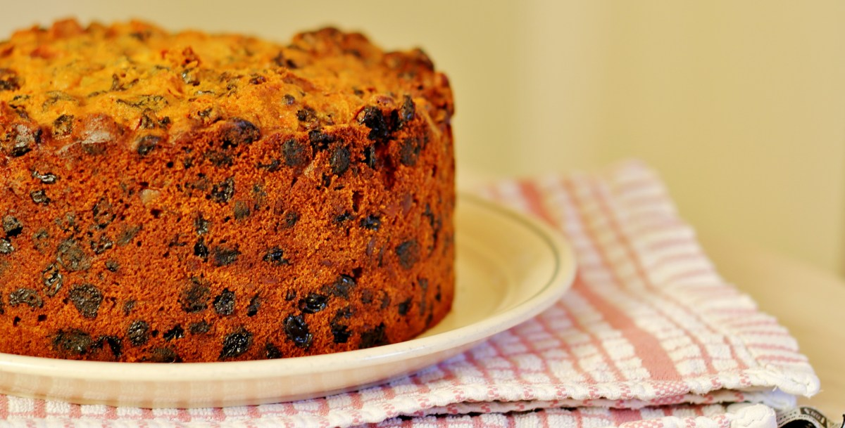A Christmas cake sits on a plate, ready to be iced.