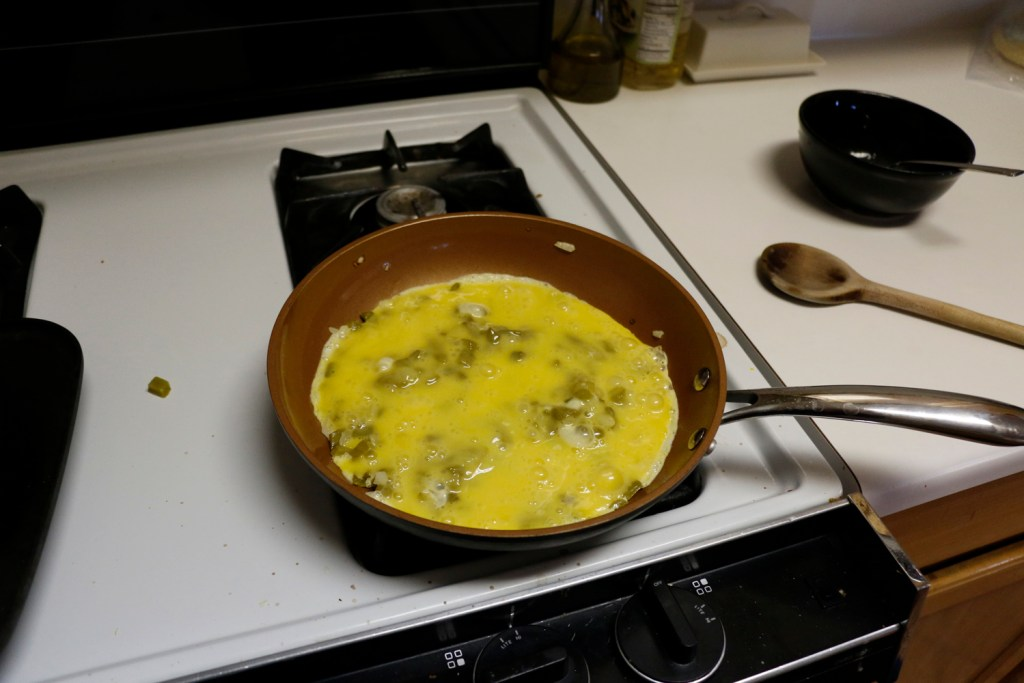 Eggs with diced cactus and onion in pan