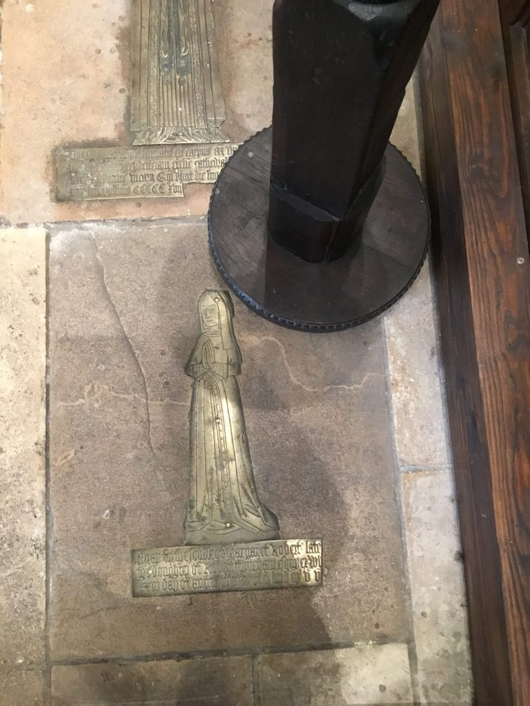 """St Mary's Church, Willesden. MemoriaMemorial brass of Margaret Roberts (1505). Image ©Andrew Pink 2016l brass of Margaret Roberts (1505). She is wearing a short gown under a dress and full skirt trimmed, with fur at the wrists and cut almost round at the neck. A broad belt, embroidered and elaborately decorated, is buckled loosely at the waist. Her head-dress - known as the """"kennel"""" or pedimented shape - confines her hair beneath a cap, stiffly wired to keep its shape. It has long sides known as """"lappets"""" which hang down past the shoulders. Image ©Andrew Pink 2016"""