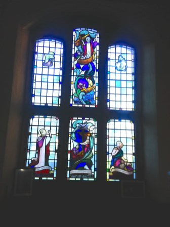 Stained glass (1947-8) by W. P Starmer (1871–1961) on the south side of the west wall of St Aldhelm's church, London N18, in 2017.