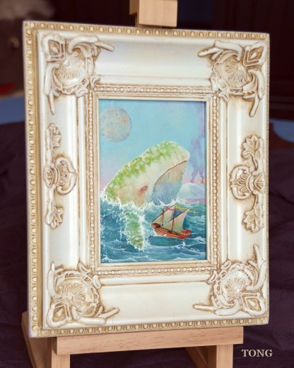 Oilpainting with ornate white frame with a white whale threating a ship