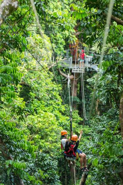 Couple moving between platforms on rainforest canopy zipline