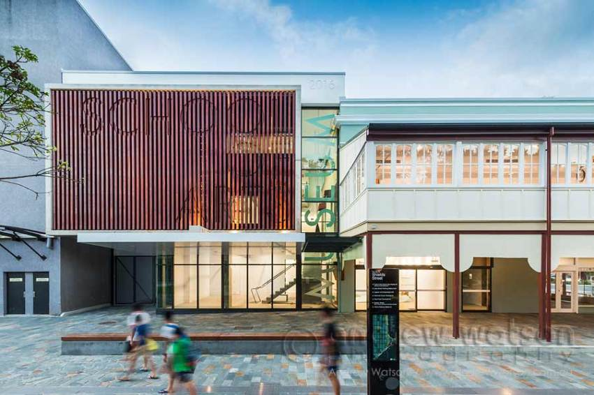 Image of people walking past the renovated School of Arts building in Cairns