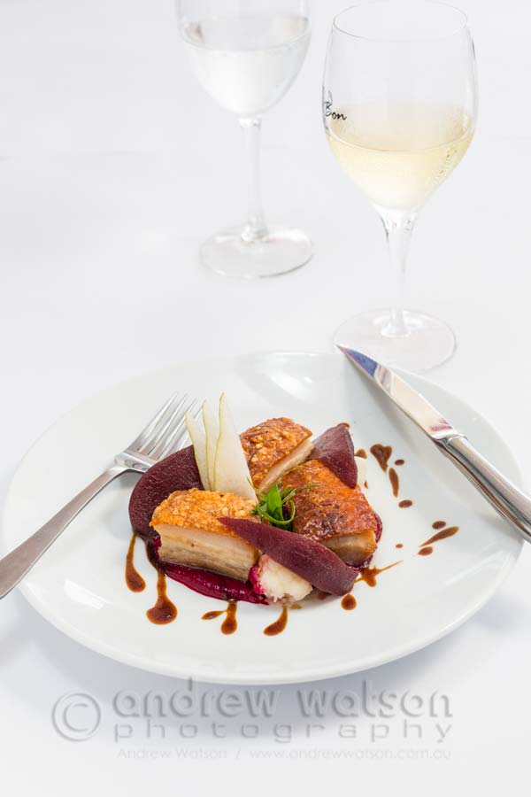 Image of French-style pork belly dish with red wine poached pear