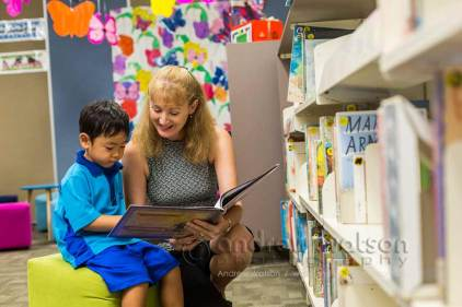 Image of teacher reading a book to a young student