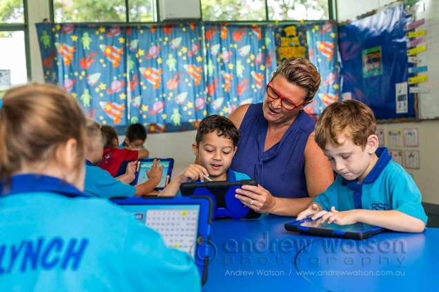 Image of school teacher helping young student using iPad
