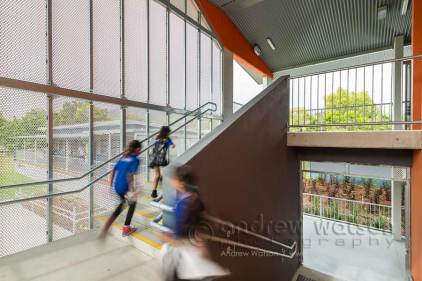 Image of school children running up staircase