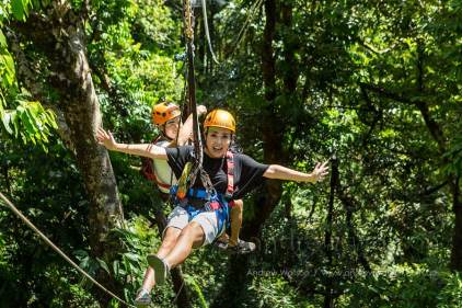 Couple having fun moving between platforms on rainforest canopy zipline