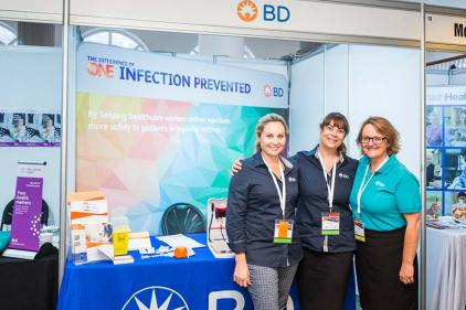 Group of conference exhibitors smiling and standing in front of booth